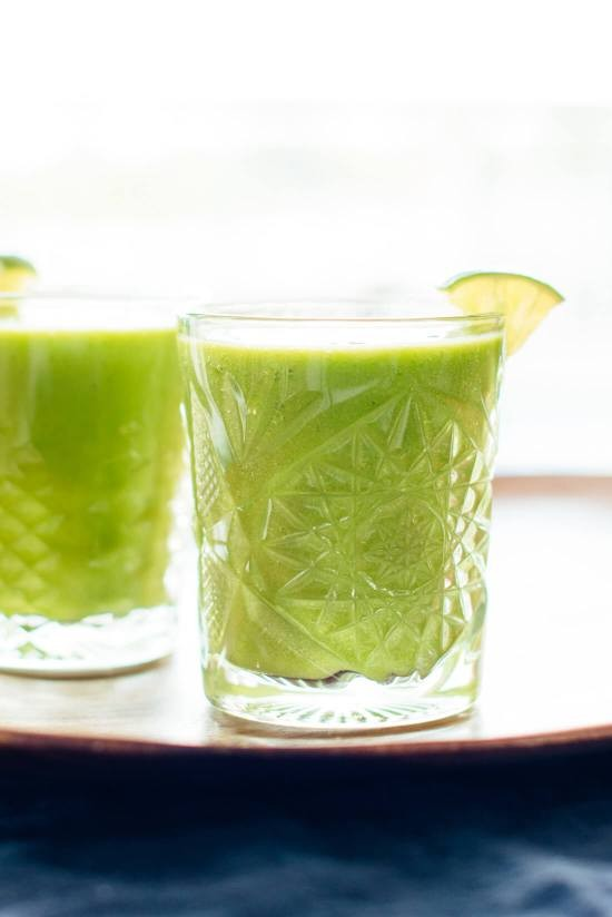 This refreshing green smoothie recipe features frozen mango and pineapple and fresh orange and lime. You can't taste the spinach, but it's good for you! cookieandkate.com